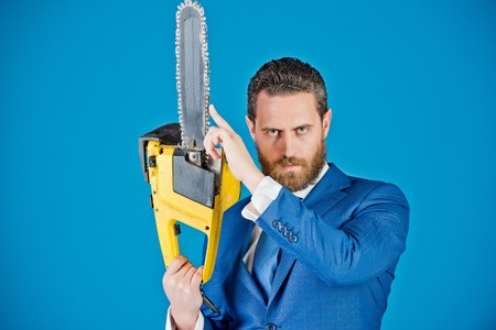 business man with chainsaw, fashion, serious businessman on blue background