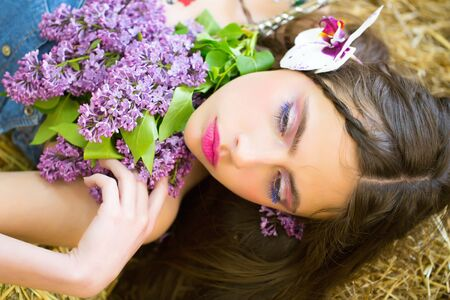 Cute girl or pretty woman, with adorable face, rosy lips, stylish makeup, blue eyelashes, mascara, and lilac and orchid flowers in long, brunette hair lying on natural hay. Countryside. Spring 版權商用圖片 - 80029275