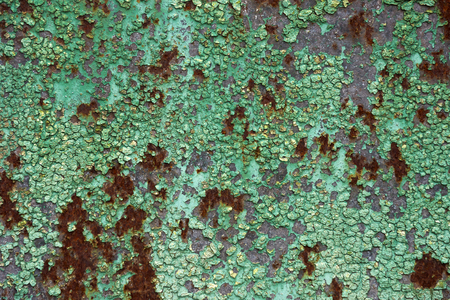 Rusty metal plate surface texture with old green paint cracking and peeling on rusted metallized background. Neglect, decay and ruin