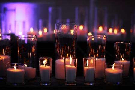 세련 된, 유리 촛대에서 어두운 나무 보드에 불꽃 반사와 함께 레코딩 왁 스 양 초. 홈 장식입니다. 휴일, 축하. 열 에너지