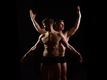 muscular twin men with bare torso and six pack in underwear with athletic body on black background, alter ego, gay and homosexual