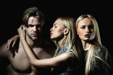 boyfriend or sexy macho with two pretty girlfriends on black background.