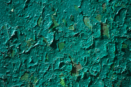 background of green paint coat, layer or covering peeling and cracking from old wall or plate with aged, grungy, rough surface texture. Loosing, removing