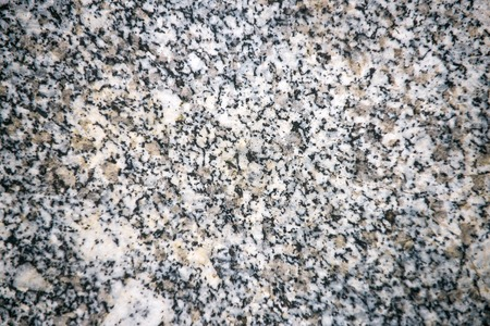 limestone or natural marble, stone slab, board or plate with white, brown and black grains, stony textured surface on abstract background. Building, design. Solidity, robustness