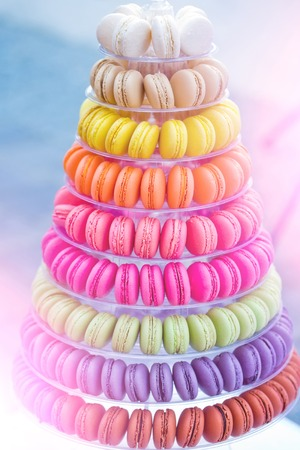 Colorful french macarons, multilevel cake pyramid, on plastic, dessert stand or plate on blurred background. Food, dieting. Birthday, anniversary, wedding celebration