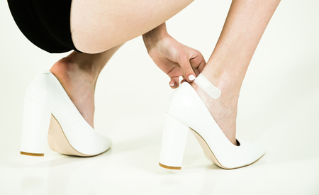 leg of woman with adhesive plaster on wound in fashionable shoes, young girl isolated on white background, skincare and health
