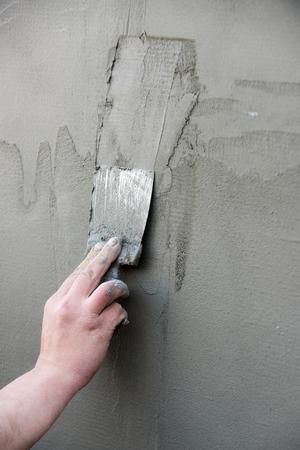 セメント壁が灰色の背景にテクスチャを表面にコートや漆喰、石膏の層を塗り男性の手で金属ヘラは。作業ツールです。建設、改修。修復・仕上げ 写真素材