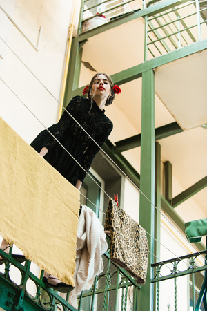 housework. girl or young woman hanging clothes on laundry line with peg or pin outdoors. Fashionable model with red lips, makeup, and rose in hair, in black lace dress on beige wall 版權商用圖片