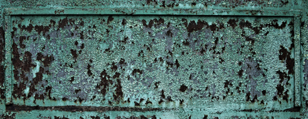 Fragment of rusty metal plate surface texture with old green paint cracking and peeling on rusted metallized background. Neglect, decay and ruin