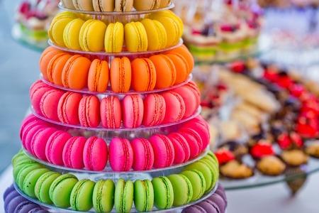 Macaron. Deliziosi macarons francesi, colorati, piramide multilivello e dessert dolce torta su piastre o stand su sfondo sfocato. Cibo, dieta. Compleanno, anniversario, celebrazione del matrimonio Archivio Fotografico - 80251886