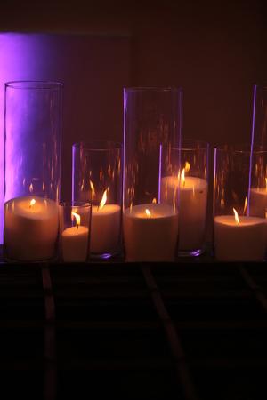 양초. 빛나는 배경에 나무 보드에 우아한, 유리 candleholders에서 불꽃 반사와 흰 왁 스의 촛불을 굽기. 어둡고 가벼운. 홈 장식입니다. 휴일, 축하. 열 에