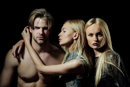 Sexy man with two blond girlfriends on black background. Pretty girl hugging muscular macho. Sad, cute woman feeling jealousy. Love triangle. Betrayal and infidelity Stock Photo