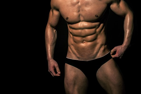 torso of sexy man with muscular body of bodybuilder athlete in underwear pants posing with bare chest and belly on black background, sport and training