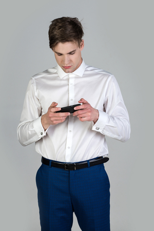 cufflink: man in white shirt and blue pants with cufflink use phone, guy has stylish hair on grey background, new technology Stock Photo