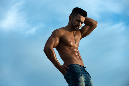 nackte brust: sexy man with muscular wet body and strong torso of bearded bodybuilder athlete in jeans posing with bare chest and belly sunny outdoor on blue sky background, copy space