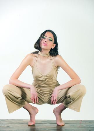 Schönheit und Mode, Mädchen, das barfuß mit naßem Haar des modernen Makes-up und des langen Brunette in der beige Unterwäsche auf dem dünnen Körper lokalisiert auf weißem Hintergrund sitzt Standard-Bild - 80238817