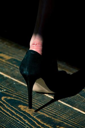 wrijven op been in zwarte modieuze schoen van glamourvrouw op houten vloerachtergrond, schoonheid en manier, skincare