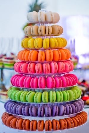 macaron cakes, tasty french dessert, on multilevel, plastic stand or plate on blurred background. Food, dieting. Birthday, anniversary, wedding celebration