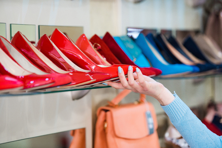 shopping showcase with female footwear or colorful shoes and hand of shop assistant or customer, beauty and fashion