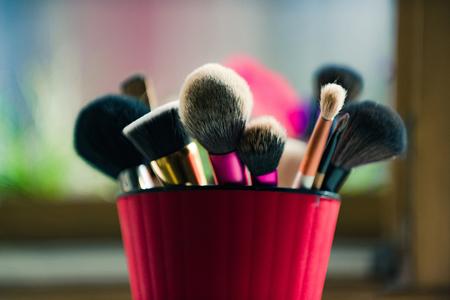 Cepillo para maquillaje de moda o cosmético en taza rosa sobre fondo borroso, moda y belleza, rostro y diseño Foto de archivo - 80326817