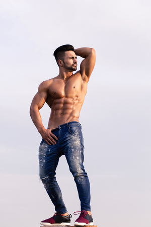 macho guy with muscular wet body and strong torso of bearded bodybuilder athlete in jeans posing with bare chest and raised hands sunny outdoor on blue sky background Stock Photo