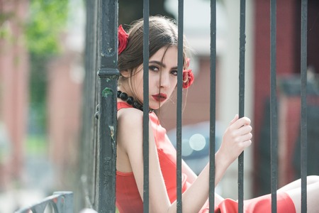 jail: girl or spanish woman with fashionable makeup and red rose flower in hair, girl in black beads accessory on iron fence background, beauty and fashion