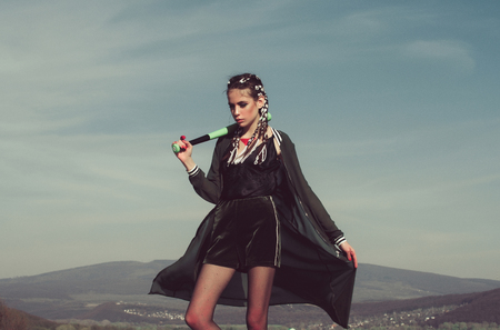 bandit woman, in fashionable, black sportswear with makeup, stylish long braids, brunette hair posing with baseball bat in hand on mountain landscape. Sport fashion and training