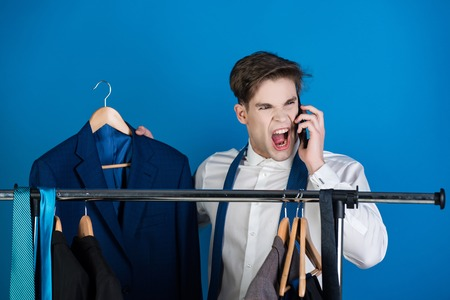 businessman or shouting angry man in shirt standing at wardrobe hanger with formal outfit speaking on phone on blue background Reklamní fotografie - 80238965