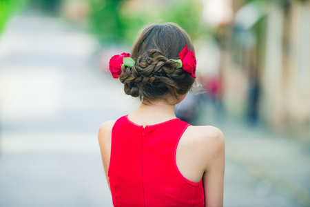 woman or cute girl, fashionable model back view with fresh red roses in stylish hair, braids, fashion hairstyle and summer dress posing on sunny day on blurred background. Hairdressing salon Stock Photo