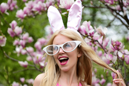 lapin sexy: Spring, easter, surprised woman or pretty girl with funny glasses, bunny ears and open mouth with long, blond hair at blossoming tree with magnolia flowers in park on sunny day on floral environment. Banque d'images
