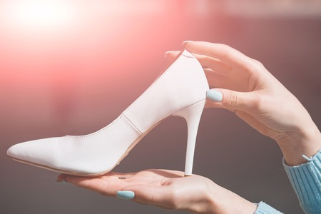 footwear or shoe white color leather on female hand on blurred background, fashion and beauty, shopping and presentation, cinderella