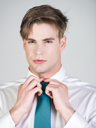 groom or young man tying a striped tie in white shirt on grey background for wedding, guy has fashionable hair and shaven face Stok Fotoğraf