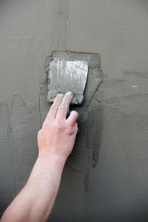 セメント壁が灰色の背景にテクスチャを表面にコートや漆喰、石膏の層を塗り金属ヘラで手します。作業ツールです。建設、改修。修復・仕上げ作
