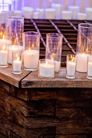 세련 된, 유리 candleholders 흐리게 배경에 목조 카운터에 부드럽고 따뜻한 레코딩에서 촛불. 따뜻한 실내. 조명. 낭만적 인 장식과 준비. 휴일, 축하