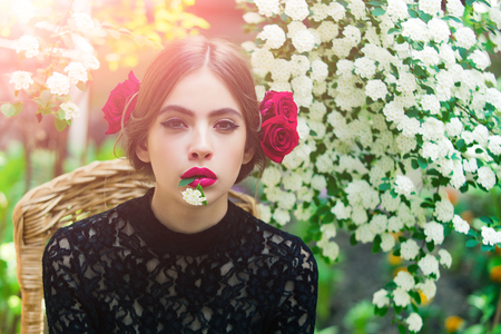 girl or pretty woman with white flower in mouth with red lips, stylish makeup on thoughtful face and roses in brunette hair on floral environment. Spring and summer. Nature beauty