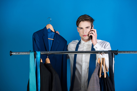 telephone interview: businessman, shaved man in shirt standing at wardrobe hanger with formal outfit speaking on phone on blue background Stock Photo