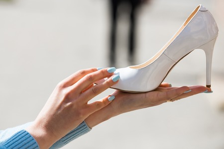 glamour shoe white color leather on female hand on blurred background, fashion and beauty, shopping and presentation, cinderella