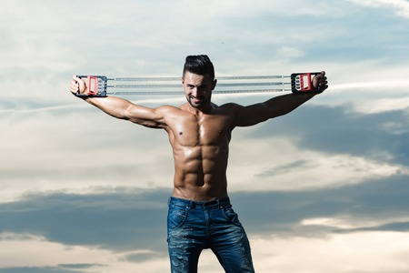 man with muscular wet body and strong torso of bodybuilder athlete in jeans workout with expander gripper on sunset sky background, copy space Stock Photo