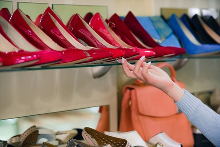 shop assistant hand at shopping showcase with female footwear or colorful shoes and customer, beauty and fashion