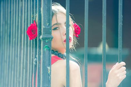 女性やファッショナブルな化粧と髪で赤いバラの花スペインの女の子, 鉄フェンス背景、美容やファッションに黒のビーズ アクセサリーで女の子