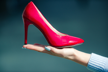 glamour shoe red color leather on female hand on blurred background, fashion and beauty, shopping and presentation, cinderella