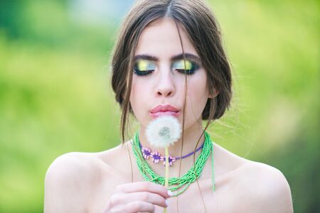 woman with fashionable makeup and beads blowing dandelion flower on natural green blurred background, beauty and fashion, youth and freshness, hairloss Imagens
