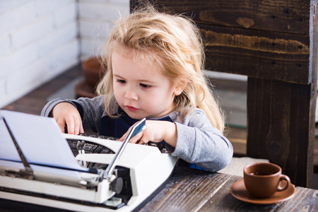 typewriter. kid or small businessman child sitting at table and typing on paper on white brick wall background, business and new technology