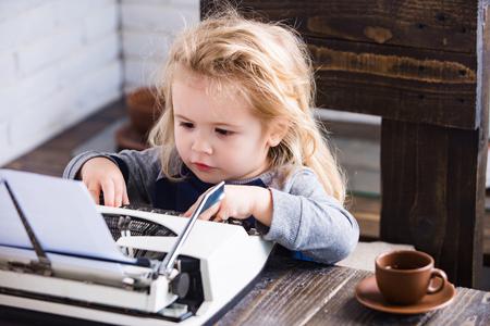 schrijfmachine. Kind of kleine zakenman kind aan tafel zitten en op papier op witte bakstenen muur achtergrond, zaken en nieuwe technologie typen