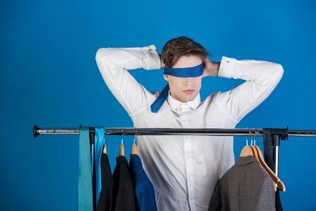 hombre con los ojos vendados. hombre de camisa blanca mantenga corbata en la cara y ojos sobre fondo azul, visión de negocios y bdsm