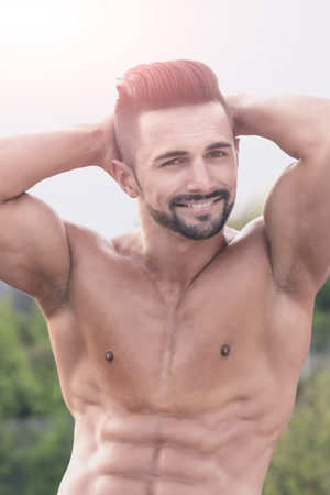 model man or happy guy with muscular wet body and strong torso of bearded bodybuilder athlete with raised hands posing with bare chest and belly outdoor on natural background