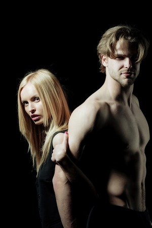 man and girl or pretty woman with blond hair, sexy guy or muscular macho with naked torso standing on black background. Couple in love. Sport and fitness