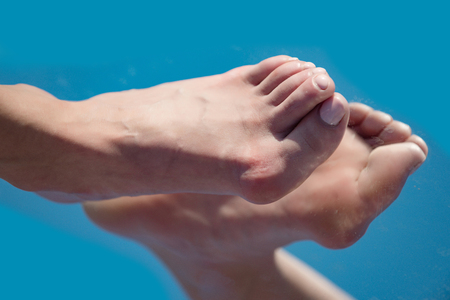 foot step. big bone on toe with pedicure reflecting in mirror on blue background, medicine and health, relax and tiredness, age and evolution, future and success