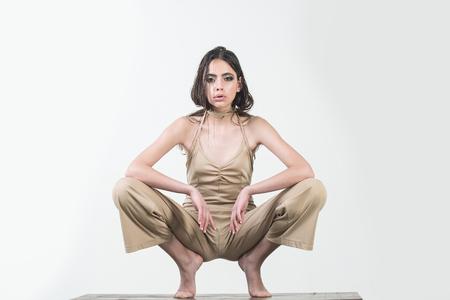 mode vrouw in ondergoed heeft over het algemeen lang haar en modieuze make-up, meisje geïsoleerd op witte achtergrond blootsvoets zitten