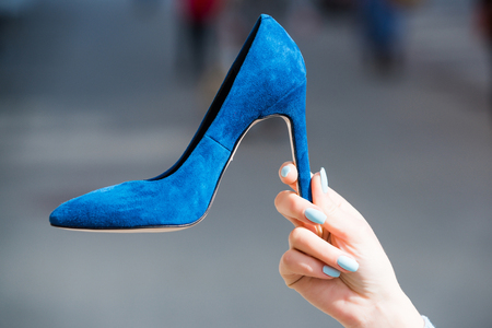 shoe blue color suede on female hand on blurred background, fashion and beauty, shopping and presentation, cinderella Фото со стока